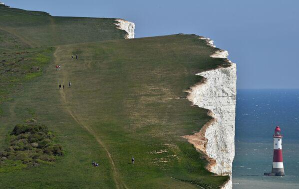 La gente cammina lungo la scogliera di Beachy Head, vicino a Eastbourne, nell'Inghilterra meridionale, il 25 aprile 2020 - Sputnik Italia