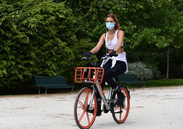 Una donna guida una bicicletta a noleggio attraverso a Milano dopo l'inizio della Fase 2, Italia, il 4 maggio 2020