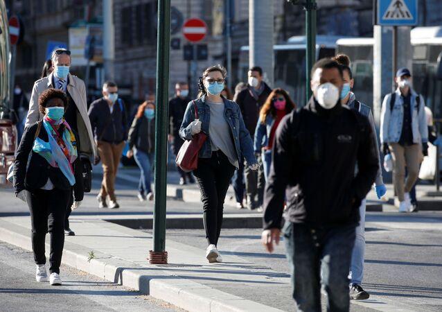Le persone che indossano mascherine protettive camminano per una strada a Roma dopo l'inizio della Fase 2, Italia, il 4 maggio 2020