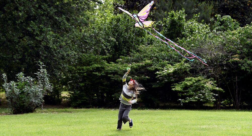 Una bambina gioca nel Parco Sempione a Milano dopo la riapertura dei parchi e l'inizio della Fase 2, Italia, il 4 maggio 2020