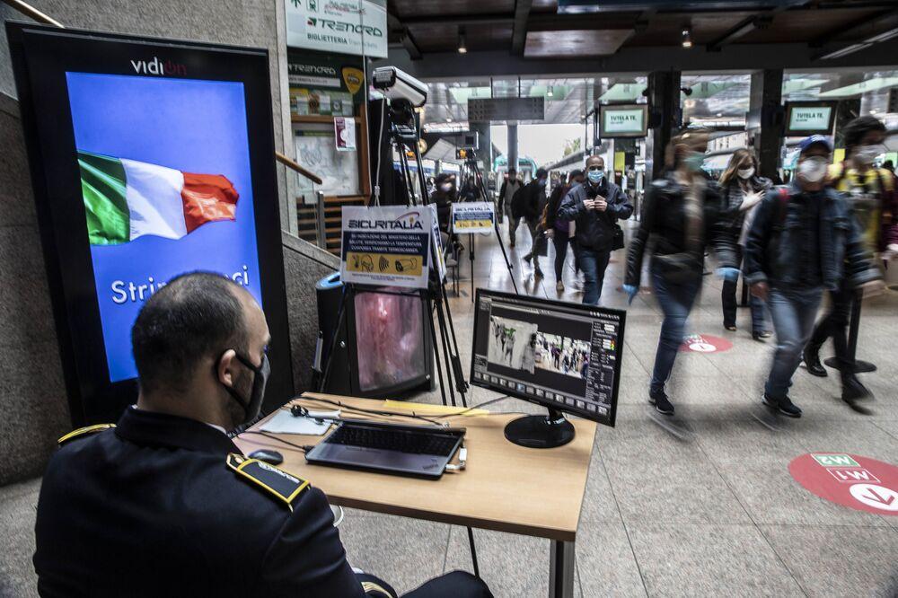 Una guardia di sicurezza controlla i passeggeri con termo scanner quando arrivano alla stazione ferroviaria di Cadorna a Milano, Italia, lunedì 4 maggio 2020