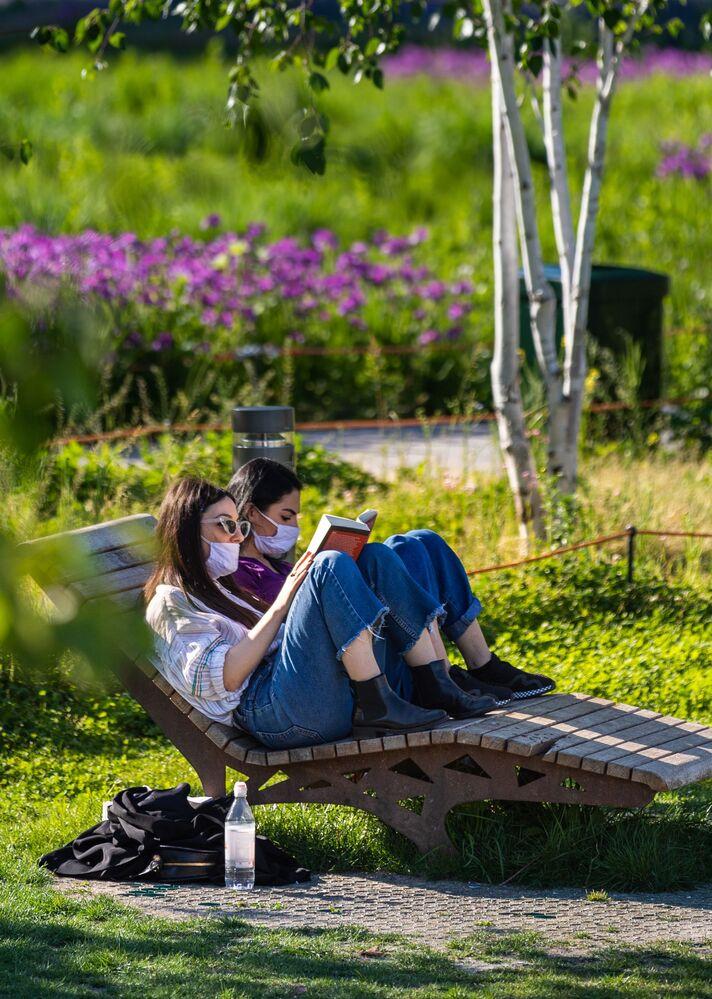 Ragazze leggono in un parco nel centro di Milano dopo l'l'allentamento delle misure anti-Covid
