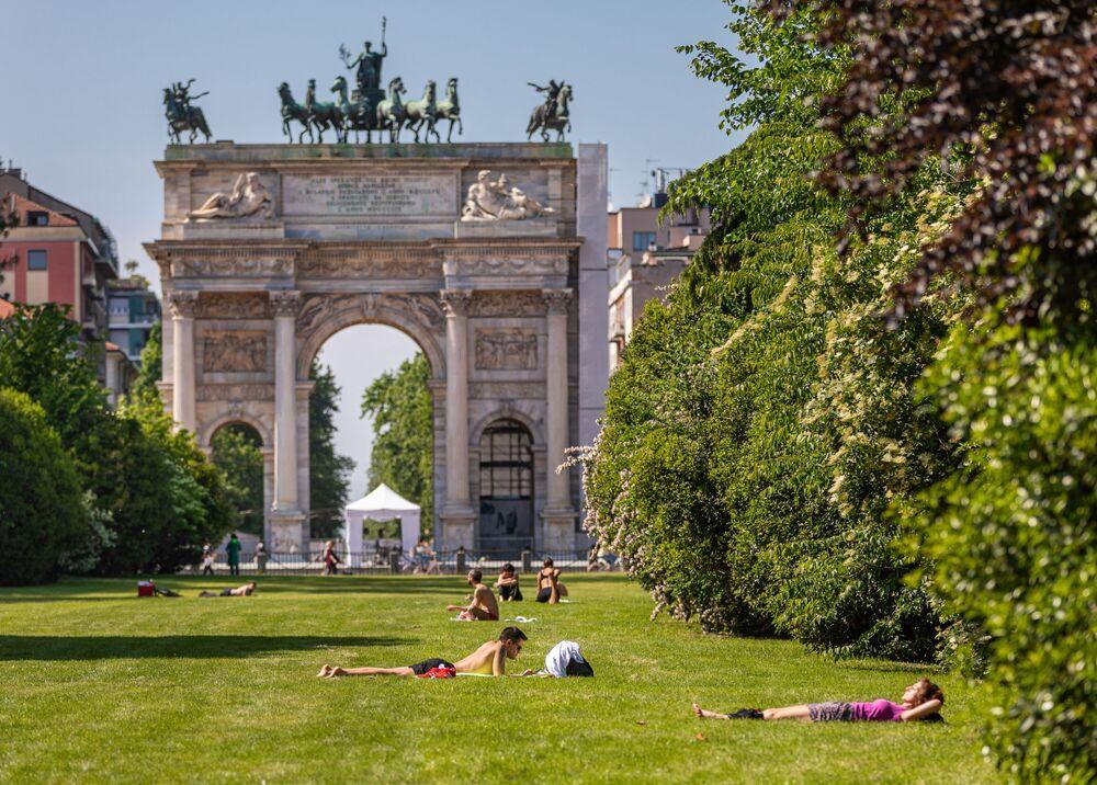 Delle persone prendono il sole in un parco di Milano dopo l'inizio della Fase 2 in Italia