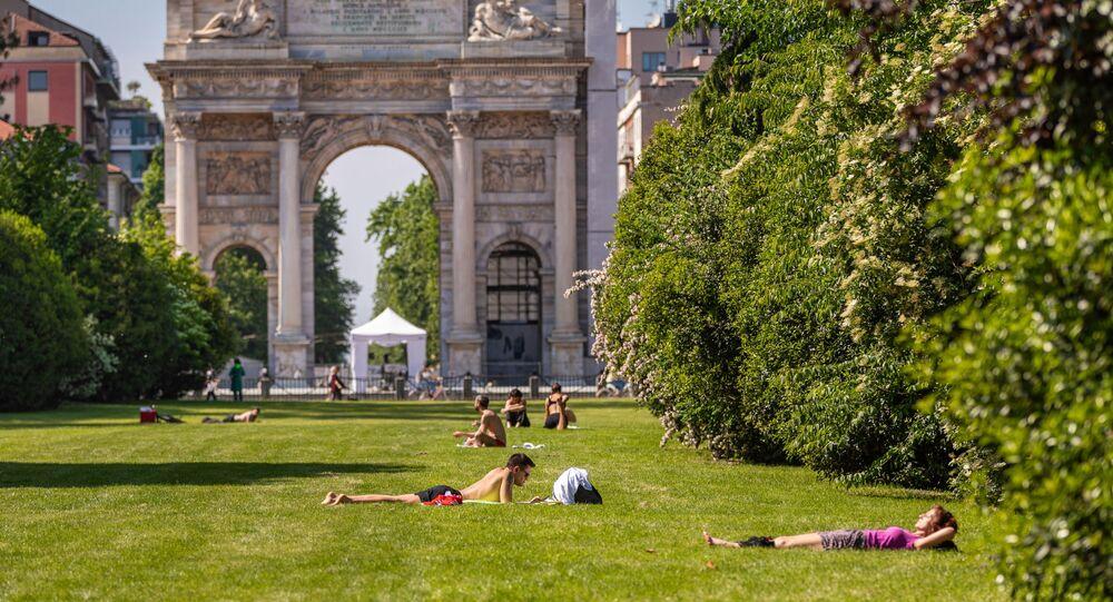 La persone prendono il sole in un parco di Milano dopo l'inizio della Fase 2 in Italia