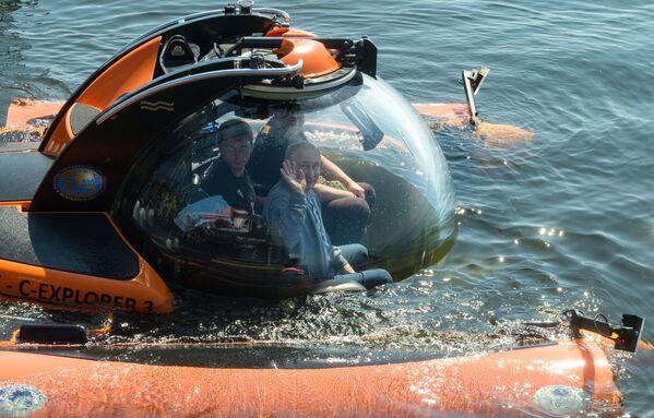 Il presidente russo Vladimir Putin visto prima dell'immersione in batiscafo sullo sfondo del Golfo di Finlandia per vedere il sottomarino Semga affondato durante la Seconda Guerra Mondiale. - Sputnik Italia