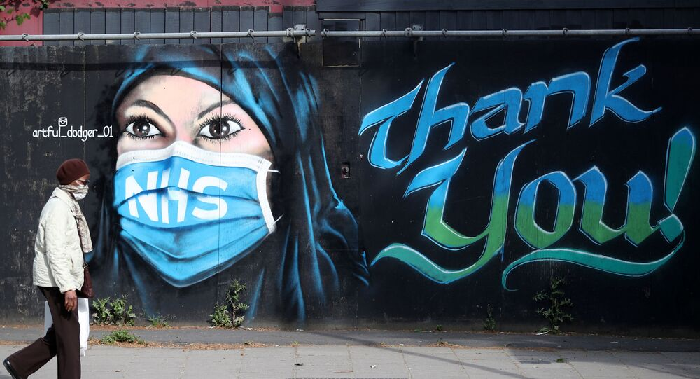 A person wearing a protective face mask walks past streetart 'NHS Dedication Mural' by The Artful Dodger (A.Dee) in Elephant & Castle, following the outbreak of the coronavirus disease (COVID-19), London, Britain, May 5, 2020