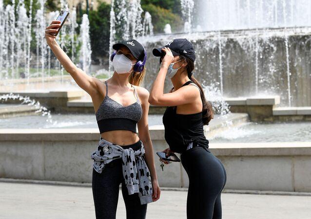 Due ragazze che indossano mascherine protettive fanno un selfie a Milano, Italia, il 4 maggio 2020