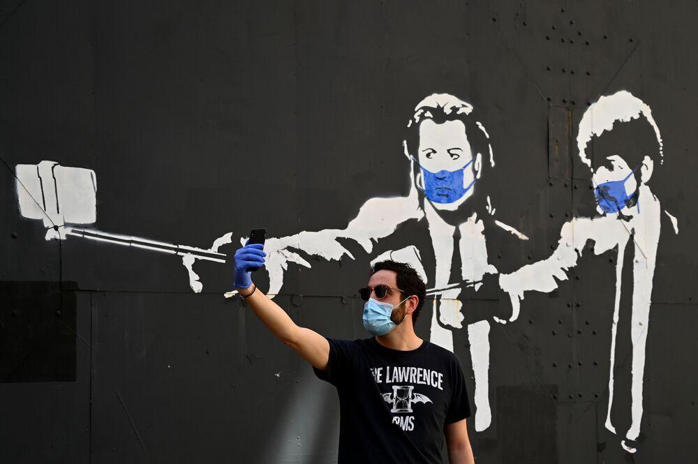 Un uomo si fa un selfie di fronte ai graffiti con gli attori statunitensi John Travolta e Samuel L. Jackson a Madrid, Spagna, il 3 maggio 2020