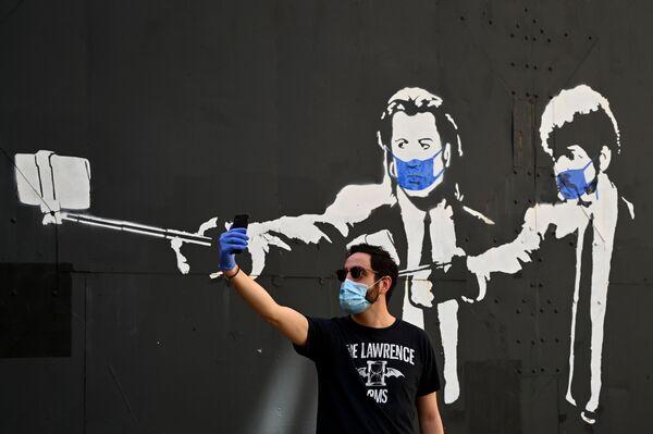 Un uomo si fa un selfie di fronte ai graffiti con gli attori statunitensi John Travolta e Samuel L. Jackson a Madrid, Spagna, il 3 maggio 2020 - Sputnik Italia
