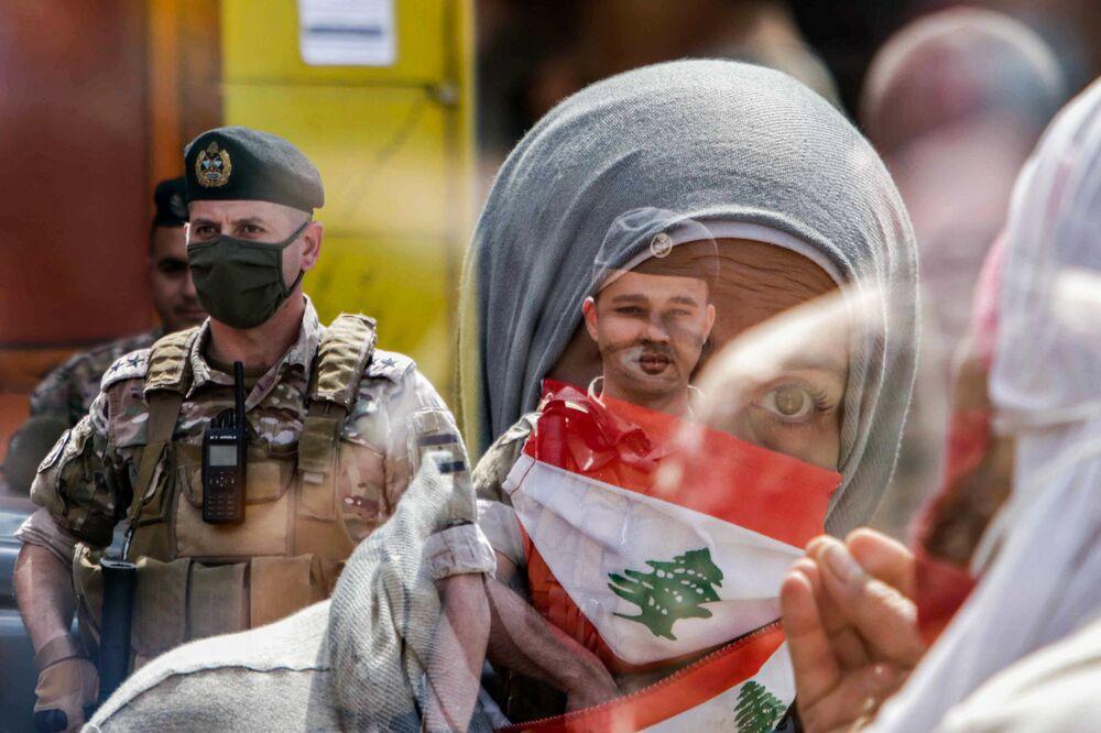 Una partecipante alla protesta e un soldato a Tripoli, il 3 maggio 2020
