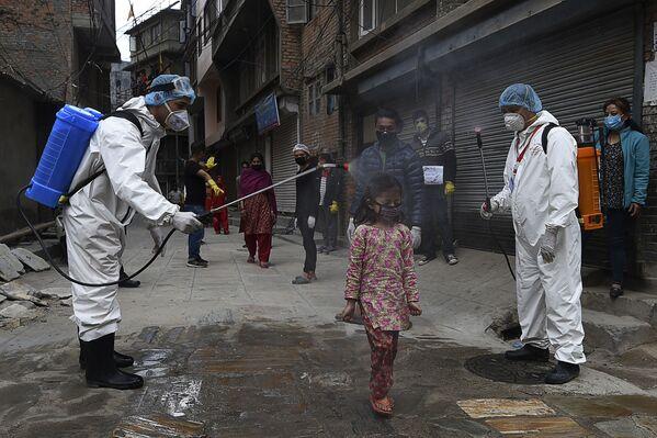 Operatori sanitari disinfettano una ragazzina a Kathmandu, Nepal - Sputnik Italia
