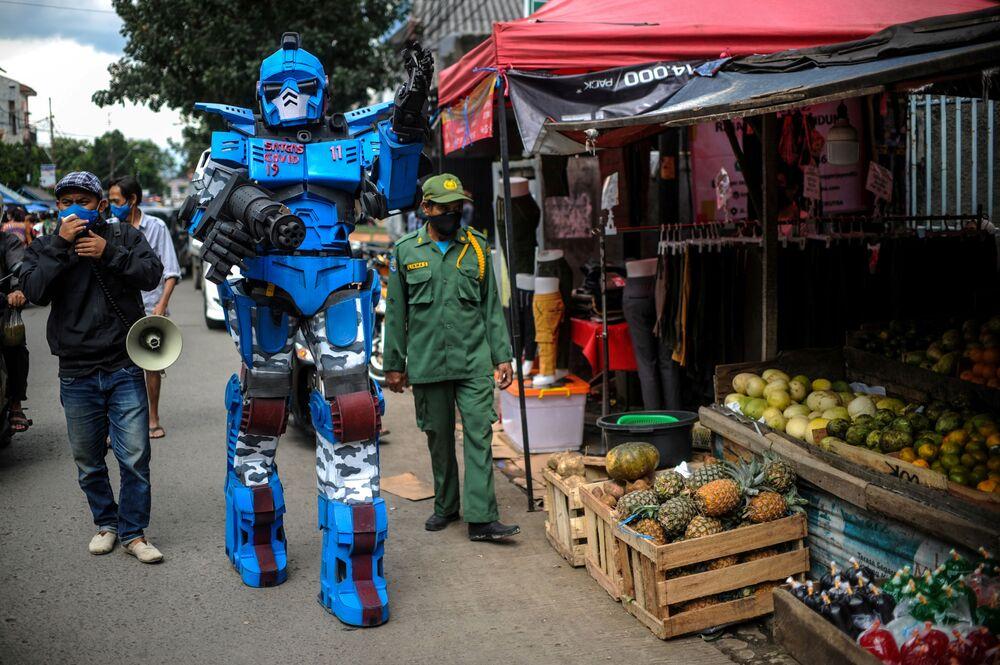 Un uomo che indossa un costume da Transformer fa appello ai cittadini affinché rimangano a casa in mezzo per lo scoppio del coronavirus, a Bandung, Indonesia, il 4 maggio 2020