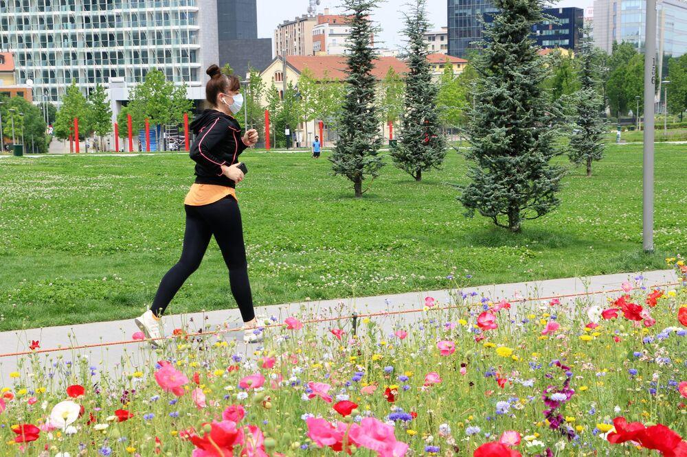 Una ragazza fa jogging in un parco di Milano dopo l'inizio della Fase 2