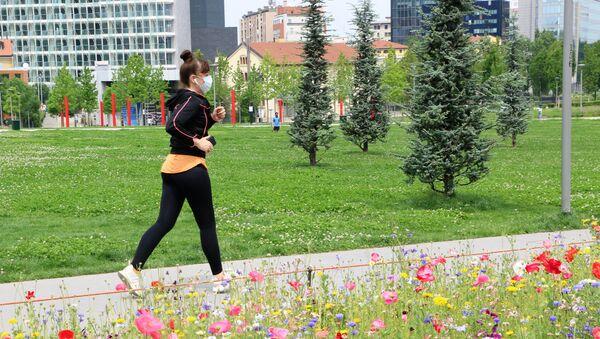 Una ragazza fa jogging in un parco di Milano dopo l'inizio della Fase 2 - Sputnik Italia