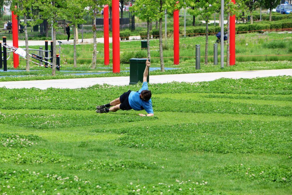 Un uomo fa sport in un parco di Milano dopo l'inizio della Fase 2