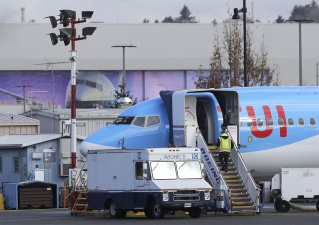 A worker walks up steps to the right of an avionics truck parked next to a Boeing 737 MAX 8 airplane being built for TUI Group at Boeing Co.'s Renton Assembly Plant Wednesday, March 13, 2019, in Renton, Wash