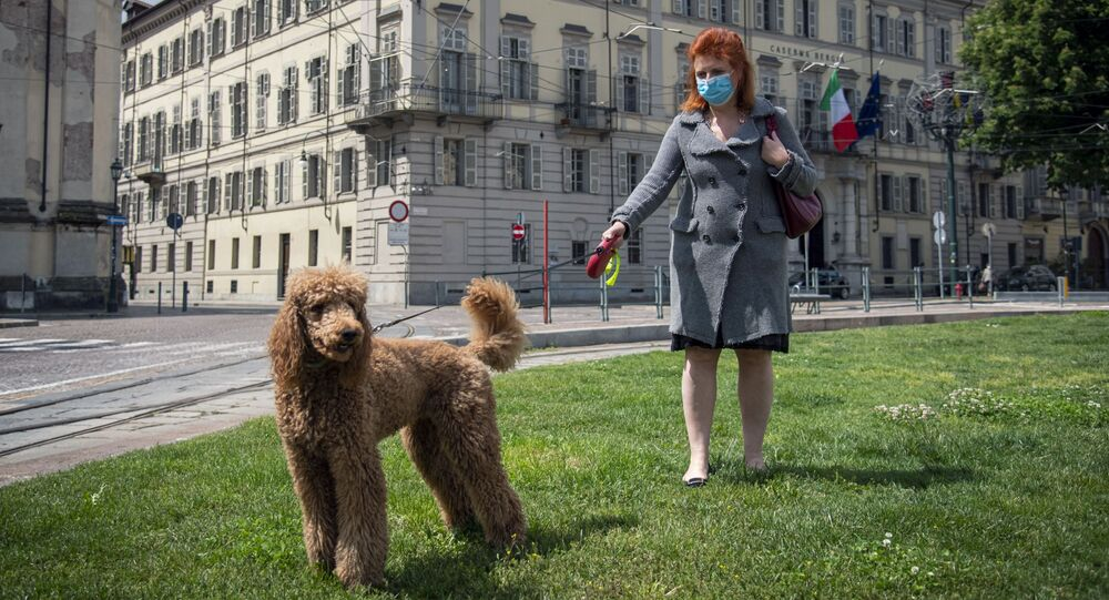 Una donna in mascherina porta a spasso il cane nel centro di Torino
