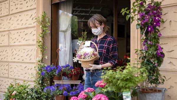 Una venditrice dei fiori in mascherina in una via di Torino - Sputnik Italia