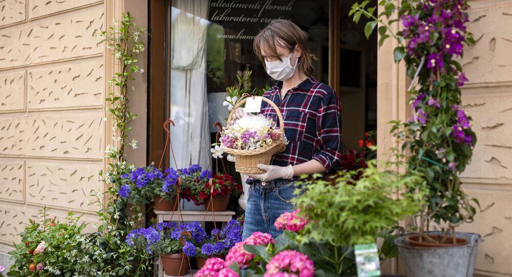 Una venditrice dei fiori in mascherina in una via di Torino