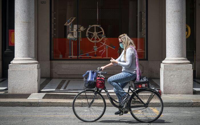 Una ragazza va in bici in Via Roma a Torino