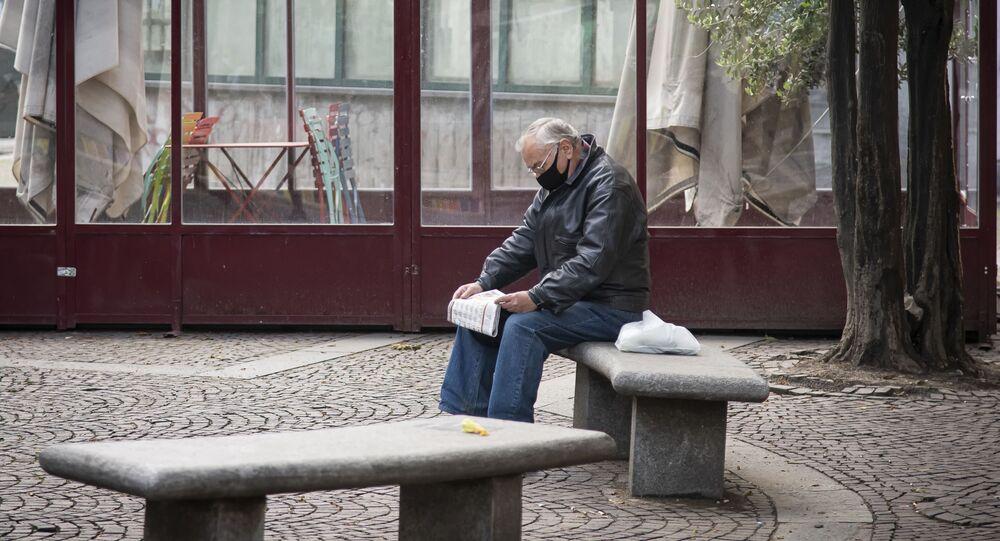 Un uomo legge un giornale in una via di Torino