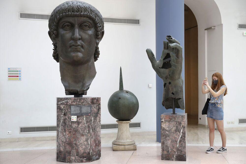 Una turista che indossa una mascherina scatta una foto della testa e della mano appartenenti alla colossale statua bronzea di Costantino, del IV secolo d.C., ai Musei Capitolini di Roma dopo riapertura dei musei italiani, martedì 19 maggio 2020