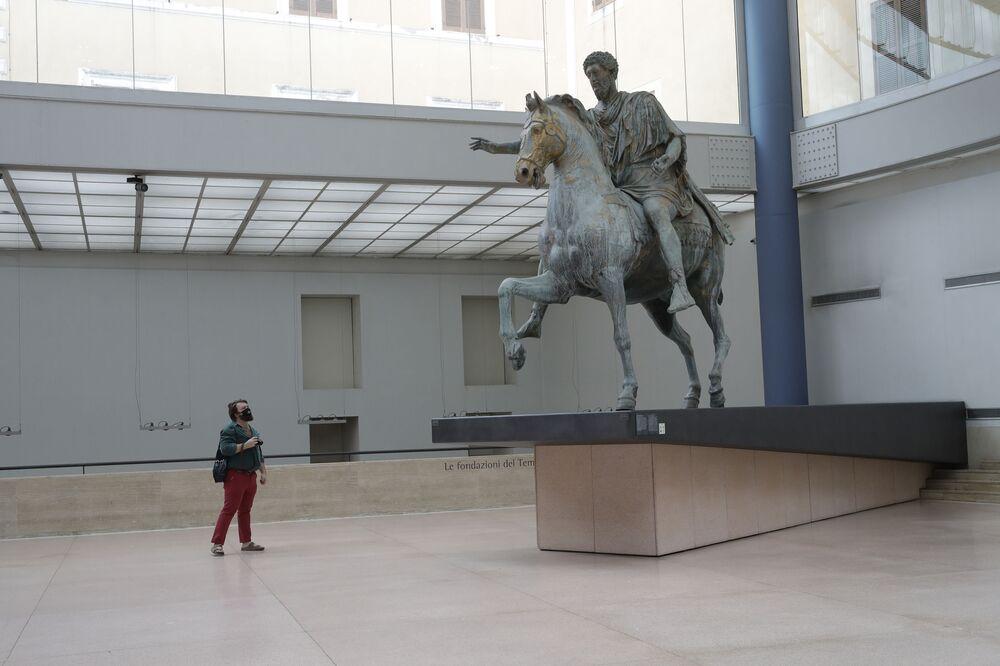 Un visitatore che indossa una mascherina per impedire la diffusione di COVID-19, guarda Marco Aurelio, una statua in bronzo di 3,5 metri, ai Musei Capitolini di Roma, martedì 19 maggio 2020