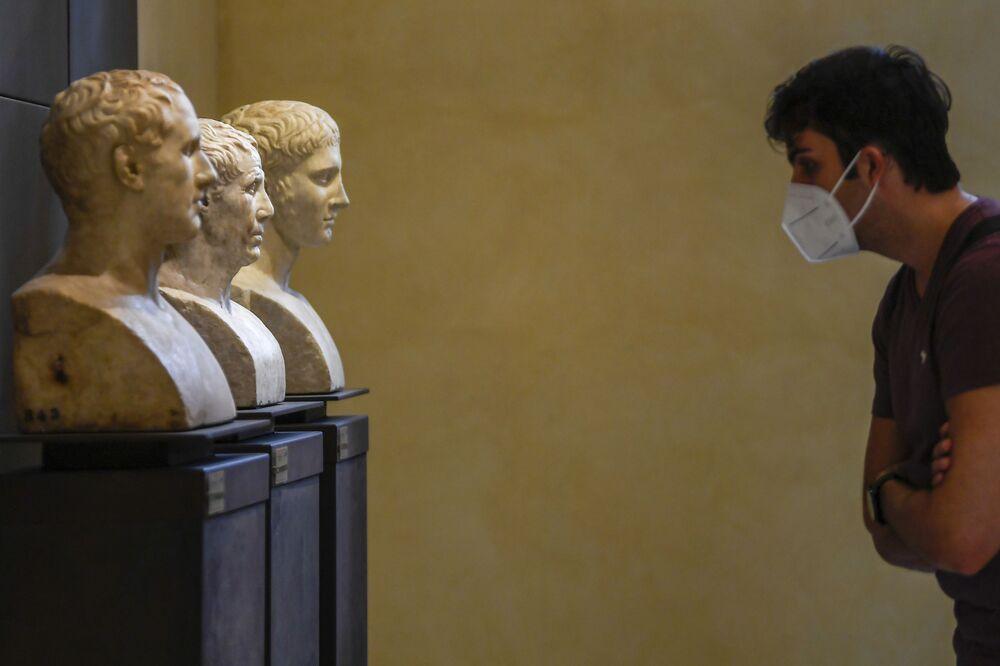 Un visitatore che indossa una mascherina facciale ammira i busti di marmo della collezione permanente ai Musei Capitolini di Roma, il 19 maggio 2020