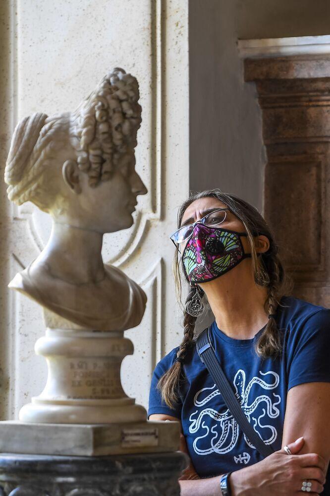 Una turista vicino ad un busto in marmo della collezione permanente dei Musei Capitolini di Roma, il 19 maggio 2020