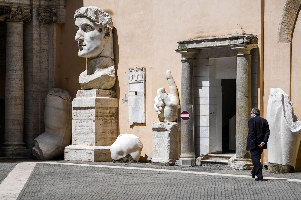 Un addetto al museo cammina accanto alle sculture antiche in un cortile dei Musei Capitolini a Roma, il 19 maggio 2020
