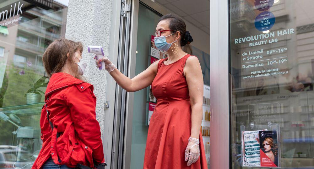 Una dipendente di un parrucchiere misura la temperatura a una cliente a Milano