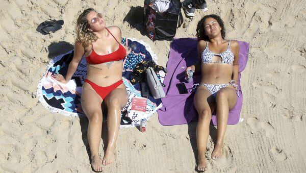 Due ragazze prendono il sole in spiaggia a Cullercoats, Inghilterra. - Sputnik Italia