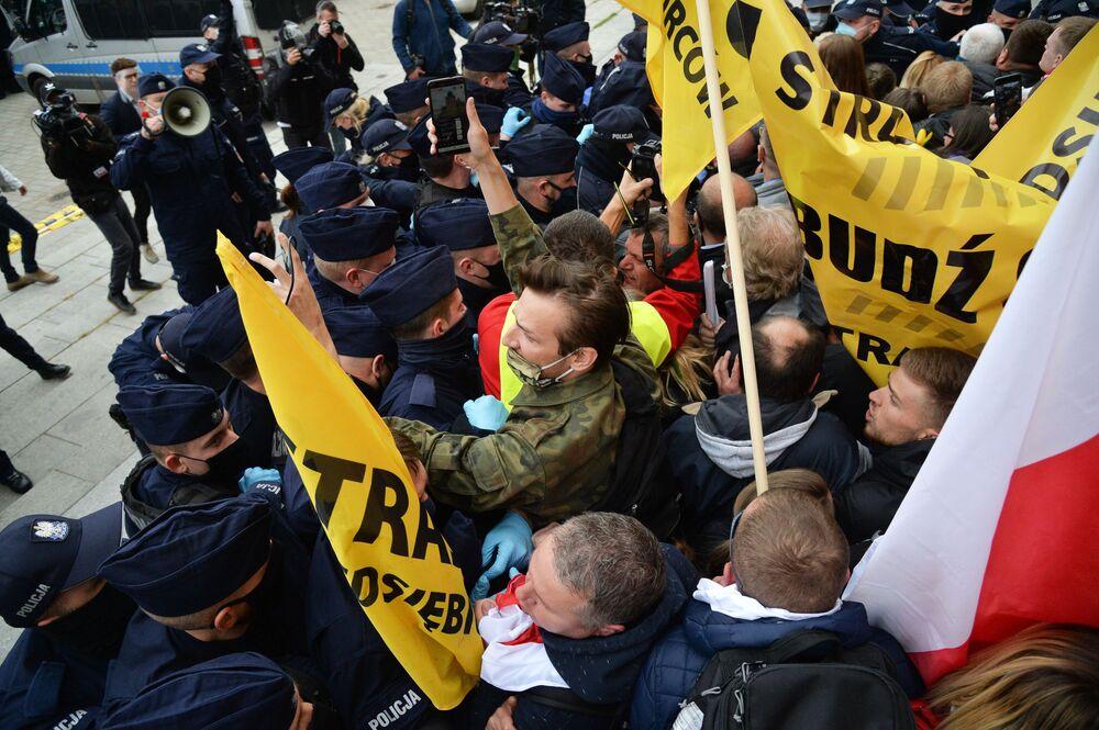 Gli scontri tra i manifestanti contro il lockdown e la Polizia a Varsavia, Polonia.