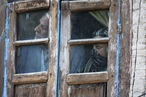 La gente guarda dalla finestra di casa a Srinagar, India. - Sputnik Italia