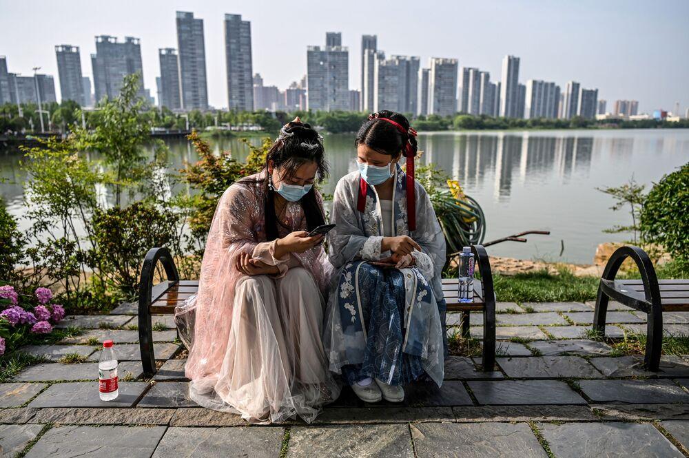 Ragazze in mascherina e costume tradizionale in un parco a Wuhan, Cina.