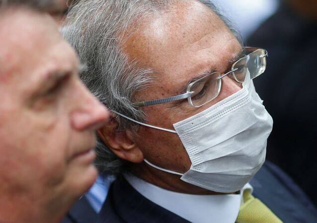 Ministro da Economia, Paulo Guedes, usa máscara protetora, ao lado do presidente do Brasil, Jair Bolsonaro, em Brasília, 7 de maio de 2020