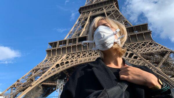 Una donna con una mascherina protettiva davanti alla Torre Eiffel  - Sputnik Italia