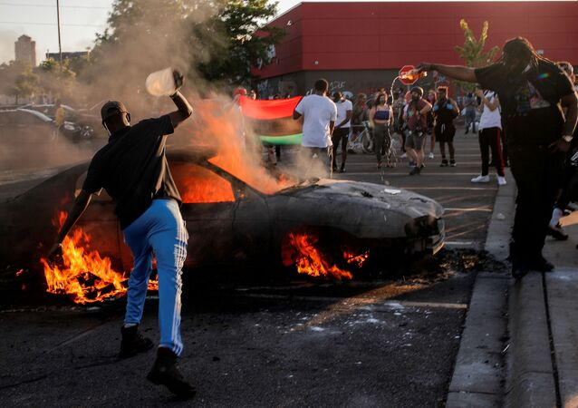People react as a car burns at the parking lot of a Target store during protests after a white police officer was caught on a bystander's video pressing his knee into the neck of African-American man George Floyd, who later died at a hospital, in Minneapolis, Minnesota, U.S., May 28, 2020