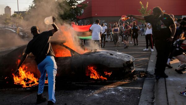 People react as a car burns at the parking lot of a Target store during protests after a white police officer was caught on a bystander's video pressing his knee into the neck of African-American man George Floyd, who later died at a hospital, in Minneapolis, Minnesota, U.S., May 28, 2020 - Sputnik Italia