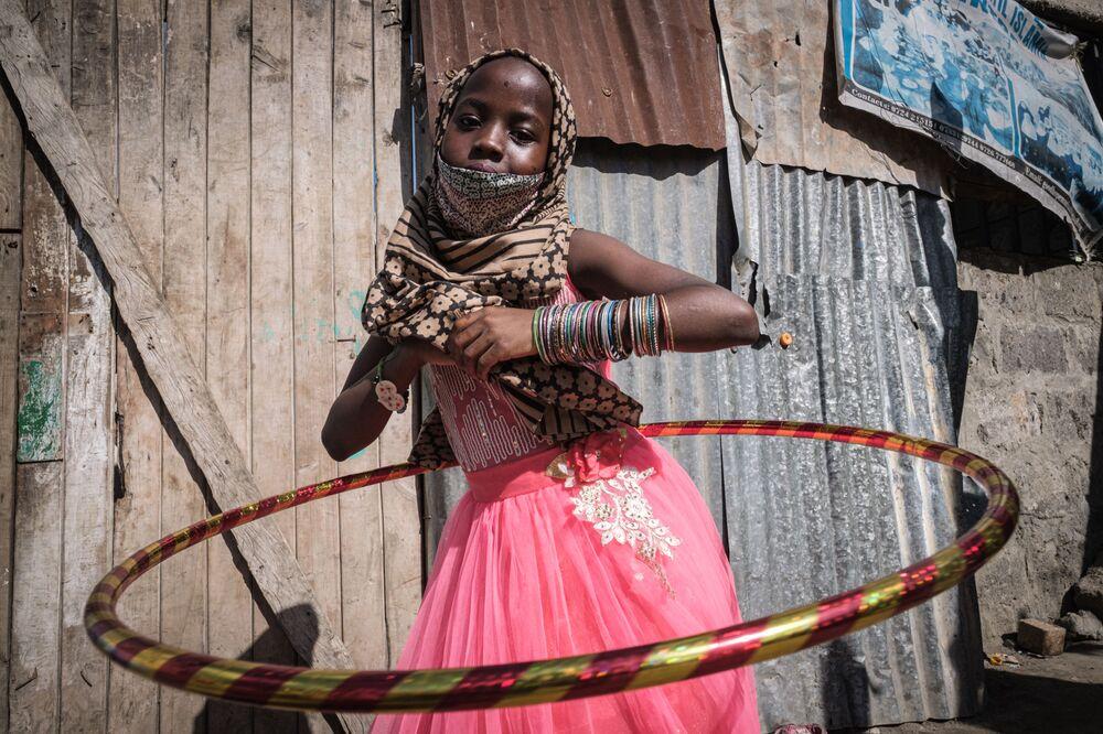 Una ragazza orfana con un nuovo cerchio durante la distribuzione del cibo e dei giocattoli agli orfani in 11 orfanotrofi in occasione di Uraza Bayram in Kenya