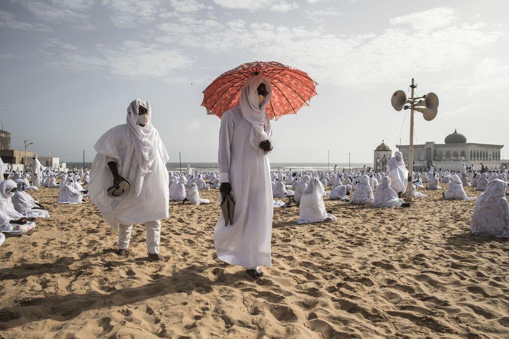 I seguaci della comunità Layene lasciano la spiaggia di fronte alla Moschea di Yoff, al termine della festa islamica di Korité, che segna la fine del mese santo musulmano del Ramadan, a Dakar, Senegal, il 24 maggio 2020