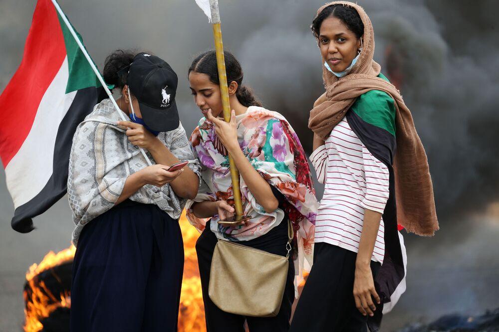 Delle donne con una bandiera durante una manifestazione a Khartum, in Sudan