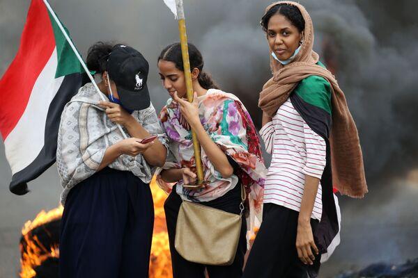 Delle donne con una bandiera durante una manifestazione a Khartum, in Sudan - Sputnik Italia