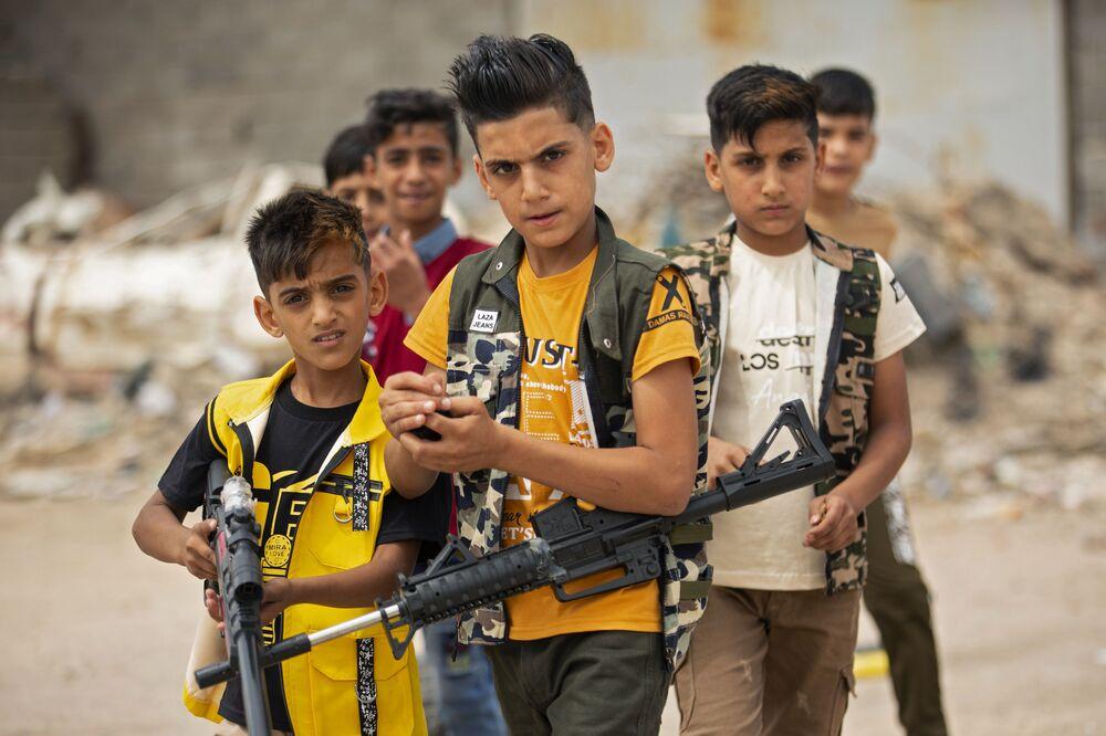 Bambini iracheni giocano con pistole di plastica nella città irachena meridionale di Bassora, il 25 maggio 2020