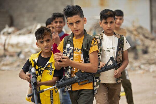 Bambini iracheni giocano con pistole di plastica nella città irachena meridionale di Bassora, il 25 maggio 2020 - Sputnik Italia
