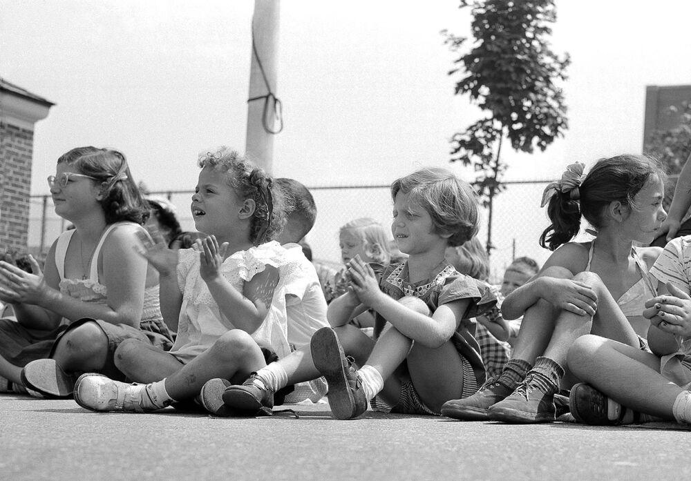 Bambini guardano uno spettacolo dei burattini in strada a New York il 12 luglio 1952.