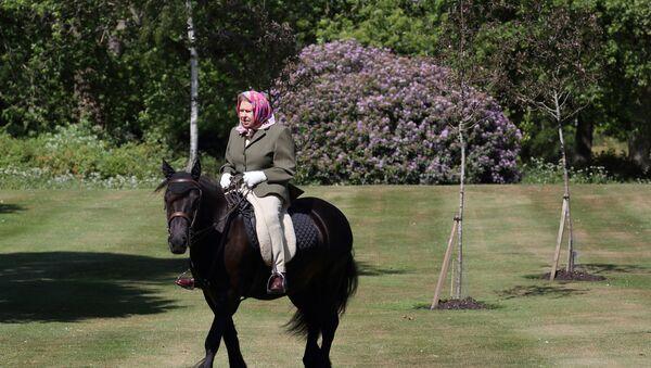 La regina Elisabetta II cavalca Balmoral Fern, un pony di 14 anni nel parco di Casa  Windsor, Londra 31 maggio 2020. - Sputnik Italia