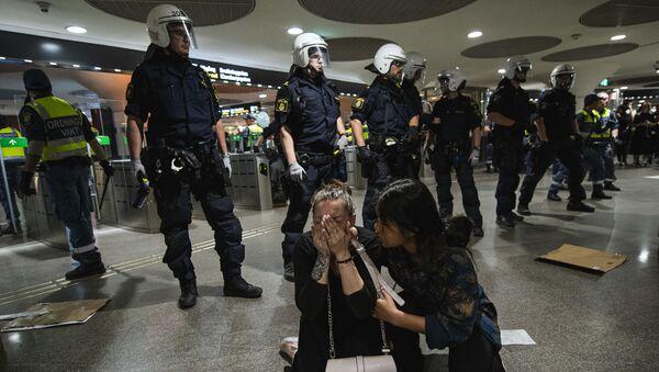 Un manifestante reagisce dopo essere stato spruzzato con spray al pepe dalla polizia in una stazione della metropolitana durante una manifestazione di Black Lives Matter a Stoccolma, in Svezia, il 3 giugno 2020 - Sputnik Italia