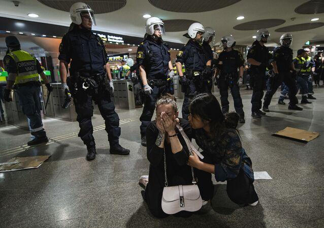 Un manifestante reagisce dopo essere stato spruzzato con spray al pepe dalla polizia in una stazione della metropolitana durante una manifestazione di Black Lives Matter a Stoccolma, in Svezia, il 3 giugno 2020