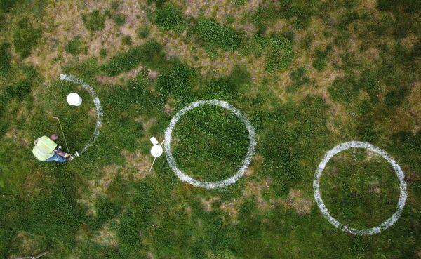 Un dipendente municipale disegna dei cerchi per il distanziamento sociale in un parco ad Istambul, Turchia. - Sputnik Italia